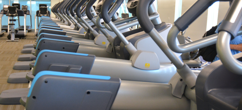 Row of ellipticals, treadmills, and other cardio machines at He