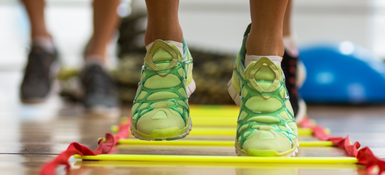 A close up of people's feet performing an exercise with a rope ladder on the floor.