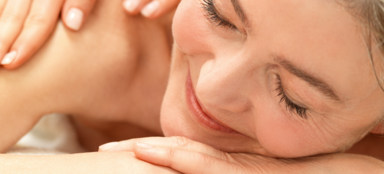 Upclose shot of a woman's reflaxed face while enjoying a massage.