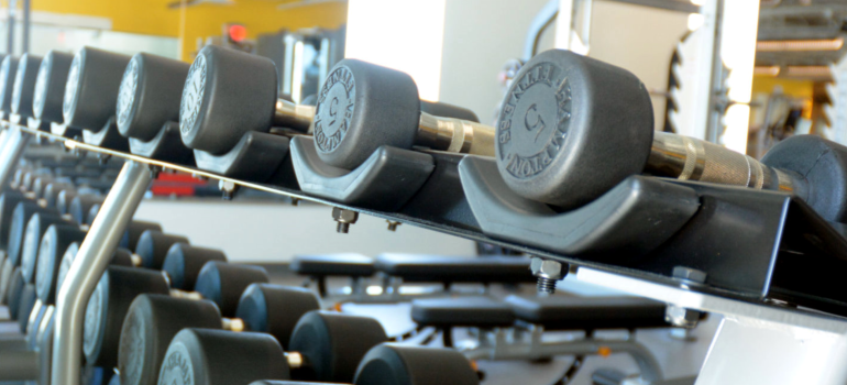 Row of dumbbells on the third, strength and functional exercise, floor at HealthSpring Fitness.