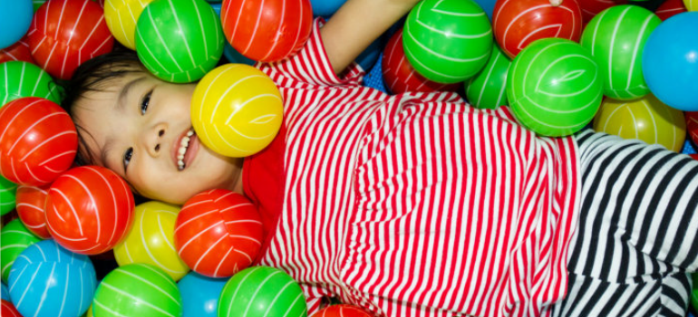 A child playing in a ball pit.